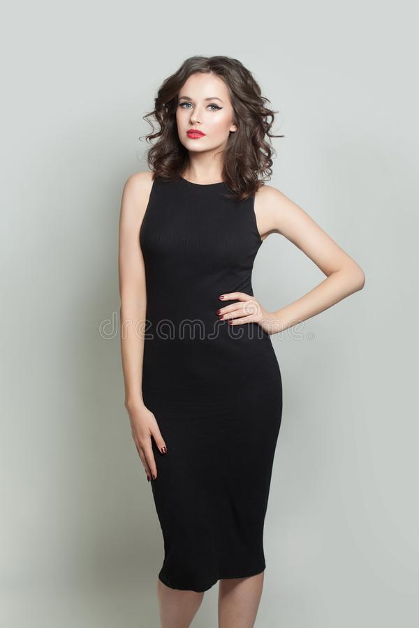 Pretty model woman in black dress posing on white background stock images