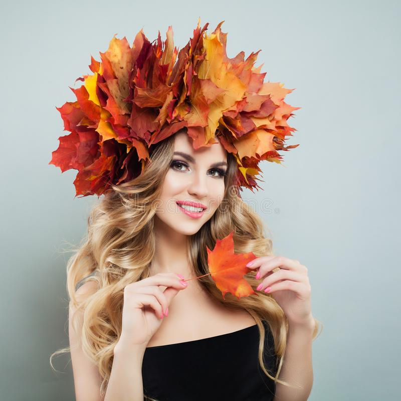 Pretty model woman holding fall leaves in hands. Beautiful model with makeup and curly hair.  royalty free stock image