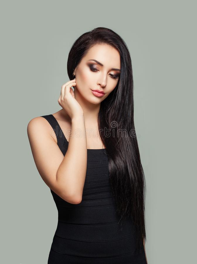Pretty model woman with long straight hair and makeup wearing black dress posing against gray wall background royalty free stock photo