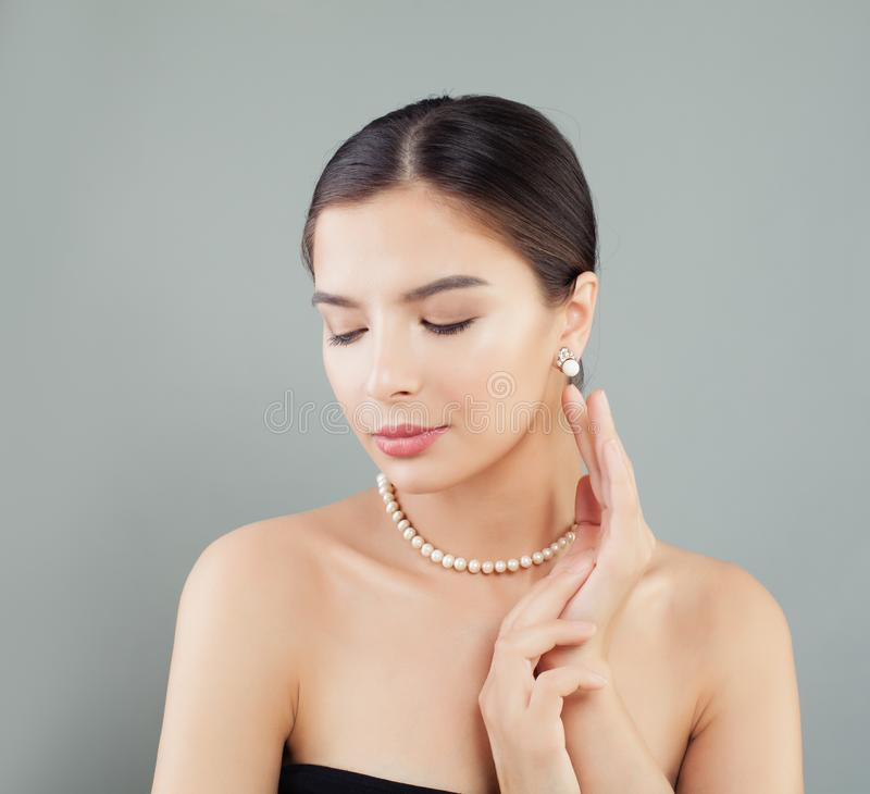 Pretty model woman in pearls necklace and earrings stock photo