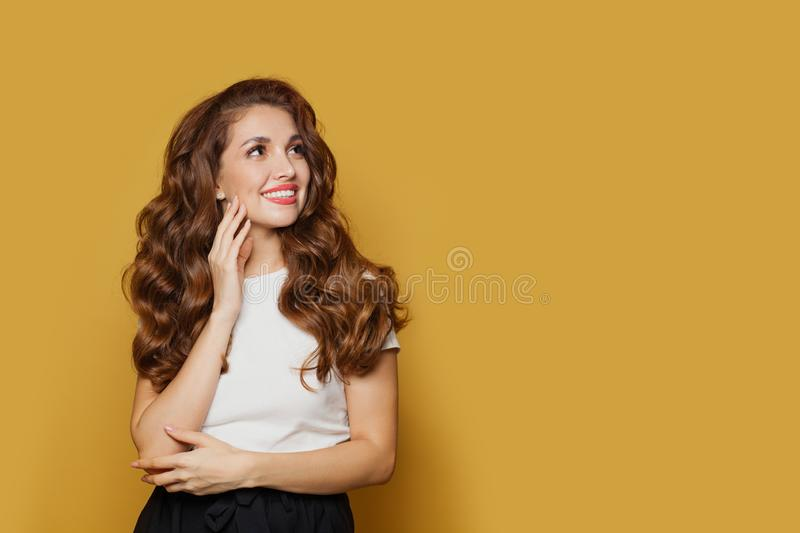Pretty model woman in white t-shirt looking up on yellow background royalty free stock image