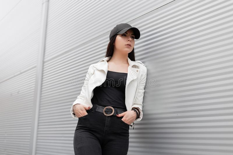 Pretty modern young woman in a white leather jacket in vintage black jeans in a stylish baseball cap is resting standing royalty free stock photos