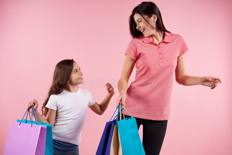 Pretty mom and daughter in casual clothes. With paper bags. Shopping and consumerism concept. Isolated on pink background royalty free stock photo