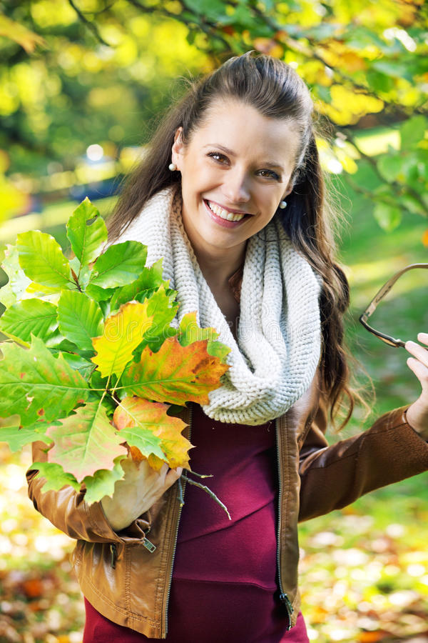 Pretty mother holding bouquet of leaves royalty free stock photography