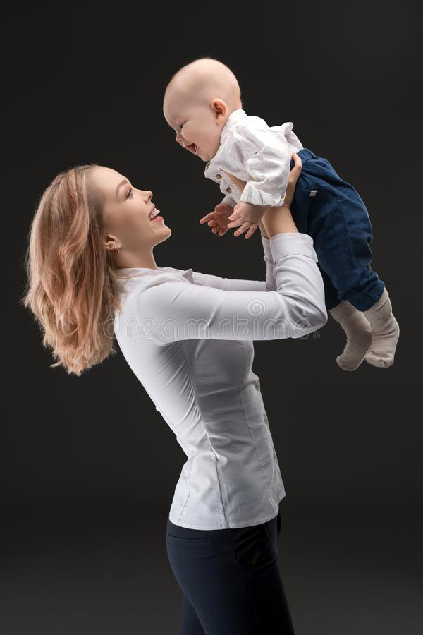 Pretty mother holding her baby profile shot stock photos