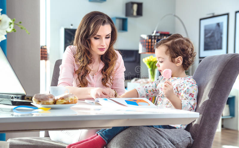 Pretty mother reading to a little daughter stock photo