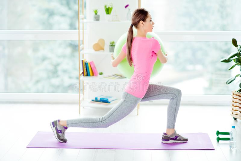 Pretty muscular energetic powerful enduring gorgeous sportive woman holding green big fit ball in hands and doing sit-ups on royalty free stock photography