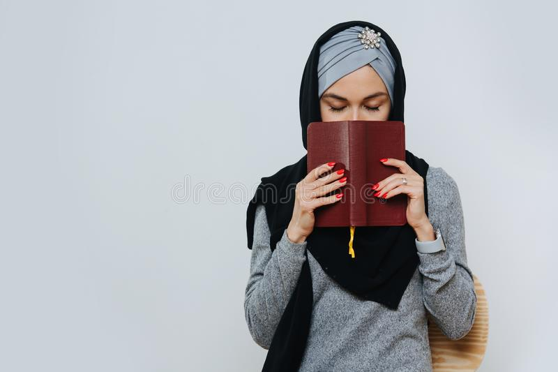 Pretty muslim woman who stands with closed eyes and covers her face with a book. Portrait of a young pretty muslim woman who stands with closed eyes and covers royalty free stock images