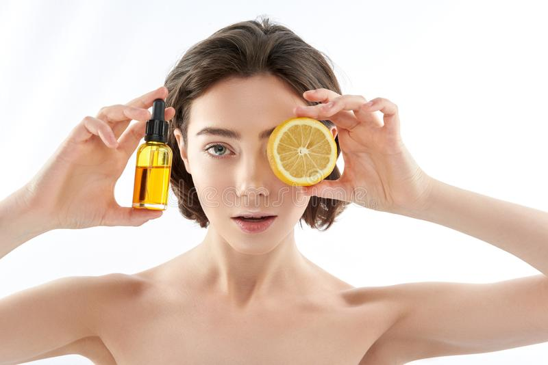 Pretty naked female with lemon and oil bottle stock photography