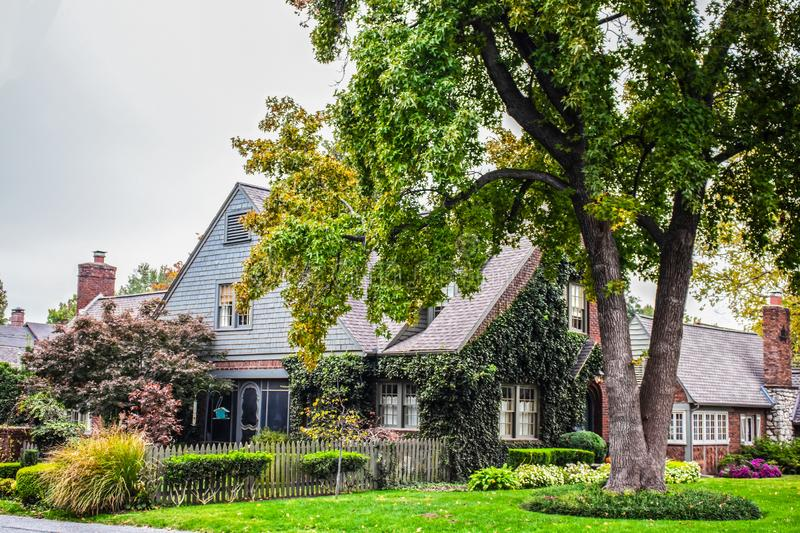 Pretty neighborhood house with wooden shingles and  bird feeders and picket fence and nice landscaping in traditional neighborhood. Pretty neighborhood house royalty free stock image