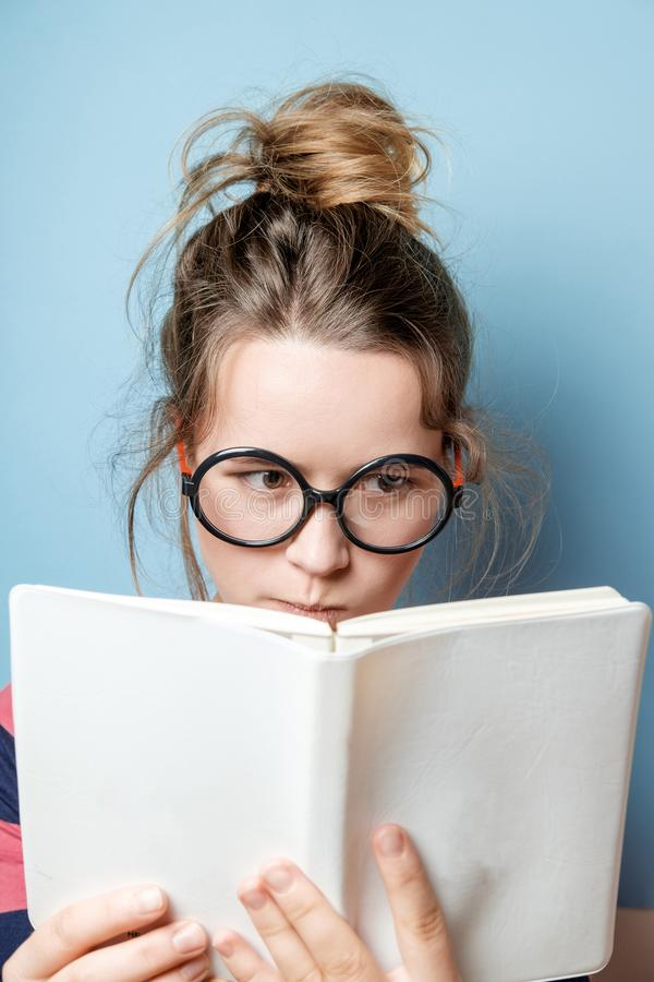 Pretty nerdy woman in spectacles reading a book against blue background royalty free stock photography