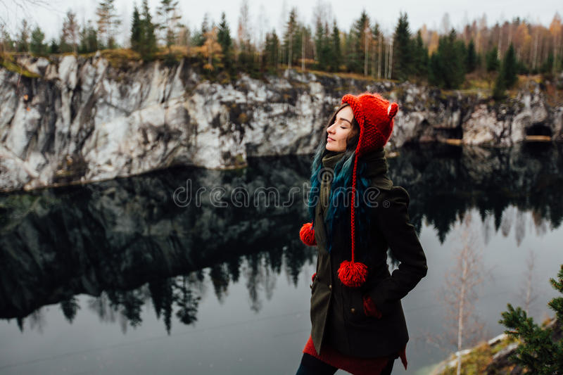 Pretty nice girl enjoy beautiful lake view from the hilltopl and good weather in Karelia. Around the rocks. Forest reflected in the water. Red knitted hat with royalty free stock photo