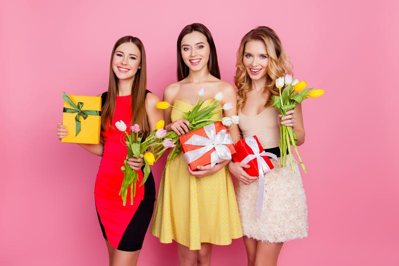 Pretty, nice trio of girls in dresses, having colorful tulips in stock image