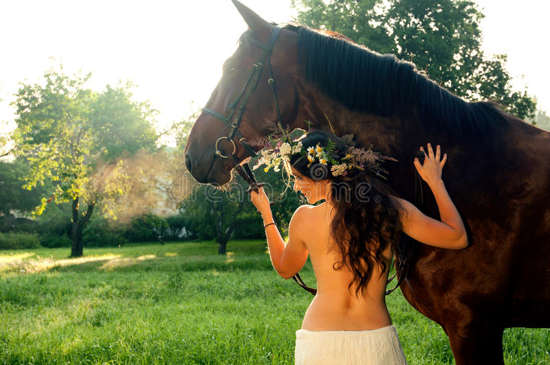Pretty nude woman with horse. Young pretty nude brunette woman with horse in summer forest stock photos