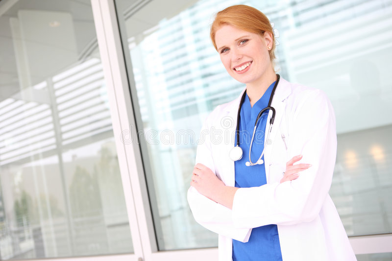 Pretty Nurse with Stethoscope. A young pretty woman nurse at hospital building stock image