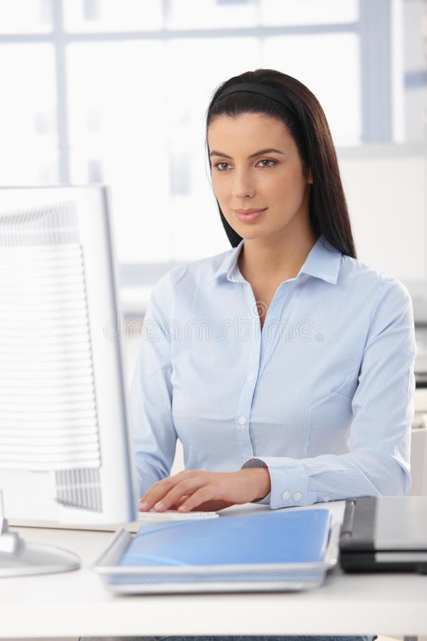 Pretty office worker at desk stock image