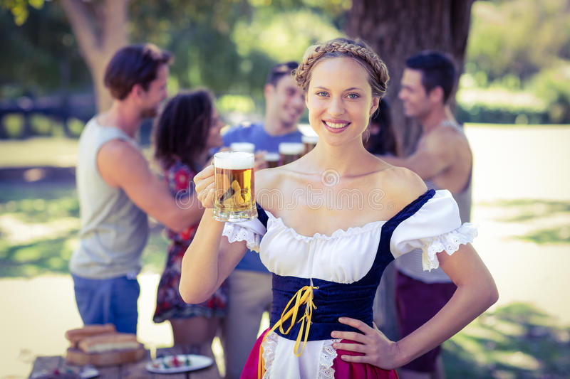 Pretty oktoberfest blonde toasting in the park stock image