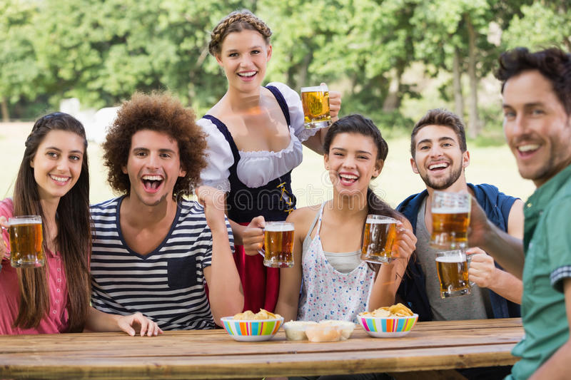 Pretty oktoberfest girl serving friends royalty free stock photography