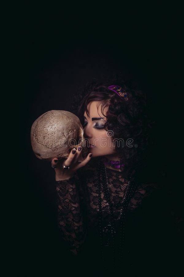 Poor Yorik. Pretty old-fashioned girl posing with skull over dark background stock photography