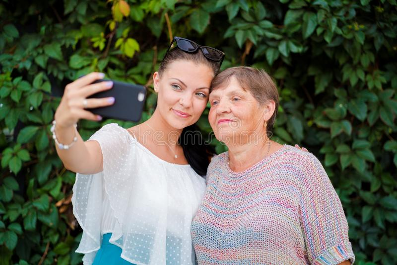 Pretty old granny and her granddaughter doing selfie outdoor, fooling around, looking at camera and laughing to. Smartphone camera. Technology, memory, family royalty free stock image