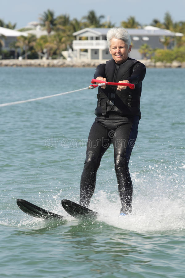 Pretty Older Lady Water Skiing by Nice House. A pretty white haired older lady water skiing on a sunny day in front of some very nice homes. Senior citizen royalty free stock photography