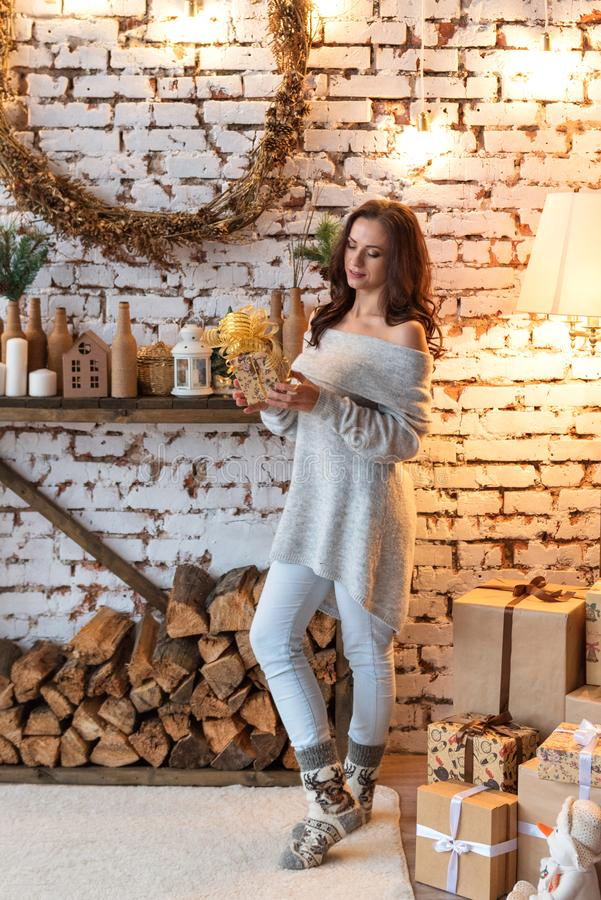 Pretty pacified young woman looking at a gift box standing near a woodpile in a retro decorated vintage New Year`s room stock photos