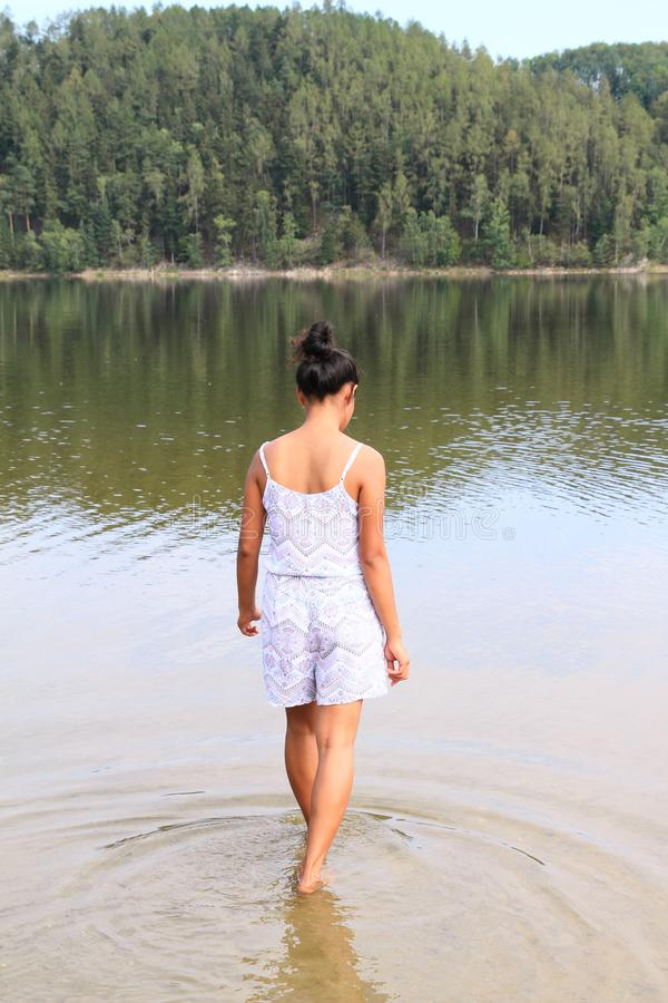Pretty girl walking into water stock images