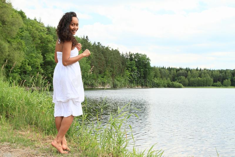 Pretty girl walking by water royalty free stock image