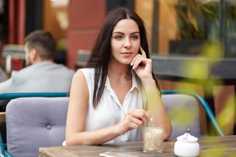 Pretty pensive brunette female looks into distance with thoughtful expression, drinks cocktail in restaurant, thinks about future. Plans, has day off or weekend stock photo
