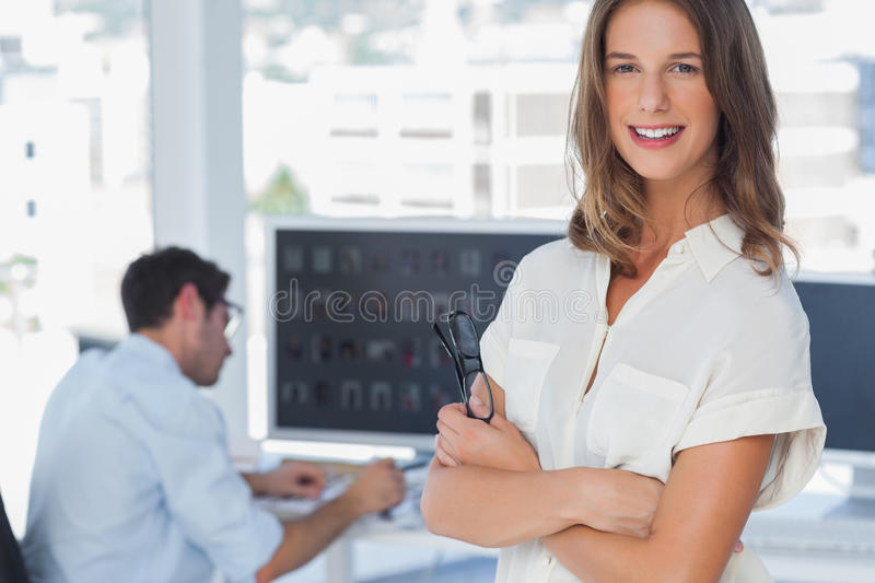 Pretty photo editor standing with arms folded. With colleague working behind stock photos