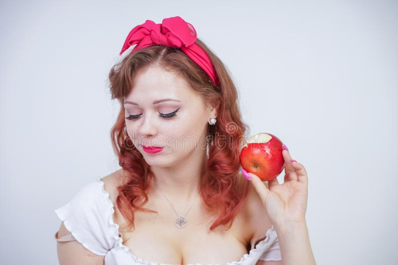 Pretty pin up caucasian young girl happy posing with red apples. cute vintage lady in retro dress having fun with fruits on white royalty free stock photo
