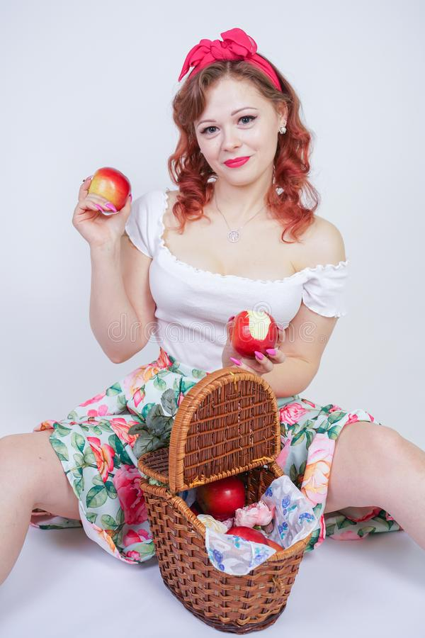 Pretty pin up caucasian young girl happy posing with red apples. cute vintage lady in retro dress having fun with fruits on white royalty free stock photos