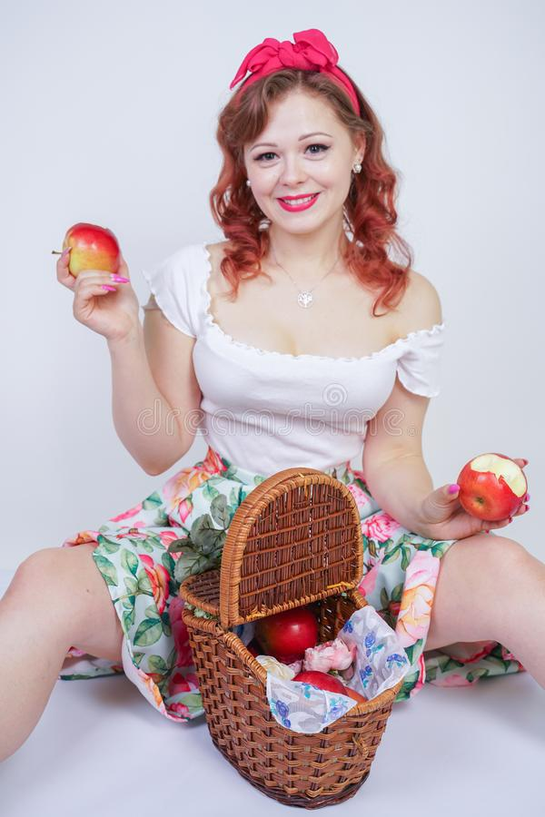 Pretty pin up caucasian young girl happy posing with red apples. cute vintage lady in retro dress having fun with fruits on white royalty free stock images