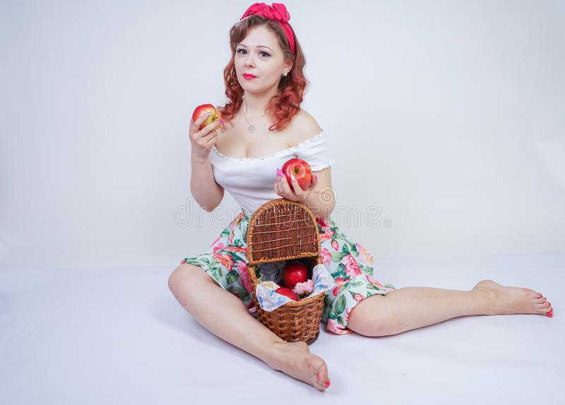 Pretty pin up caucasian young girl happy posing with red apples. cute vintage lady in retro dress having fun with fruits on white stock image