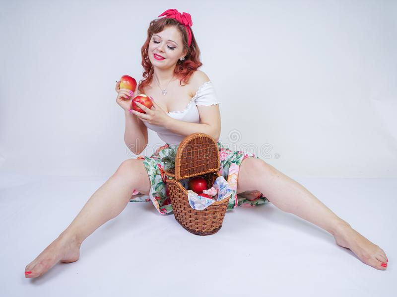 Pretty pin up caucasian young girl happy posing with red apples. cute vintage lady in retro dress having fun with fruits on white stock photos