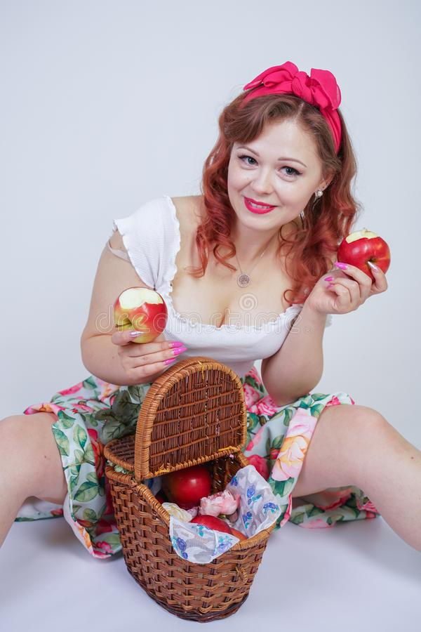 Pretty pin up caucasian young girl happy posing with red apples. cute vintage lady in retro dress having fun with fruits on white royalty free stock image