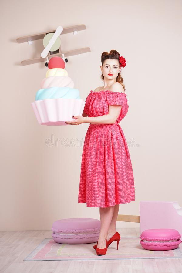 Beautiful elegant pin up woman wearing red polka dot dress posing with giant sweets alone stock images