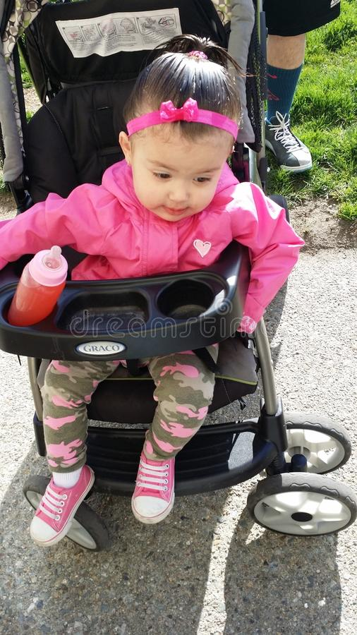 Pretty in pink. Baby girl dressed in pink and army during the spring time headingnto the park stock photo