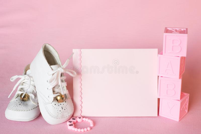 Pretty Pink Baby Girl Shower Invitation Card or Birth Announcement with vintage white shoes on Pink Cloth Background with room or royalty free stock photography
