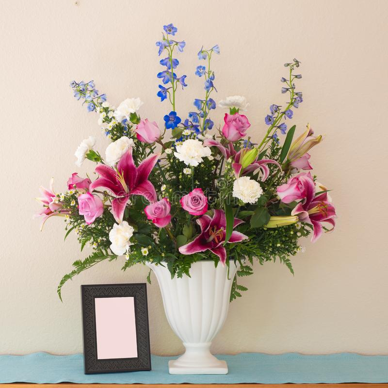 Pretty Pink and Lavender Flower Bouquet in White Vase with Blank Picture Frame with room or space for your words, text or copy. S royalty free stock image