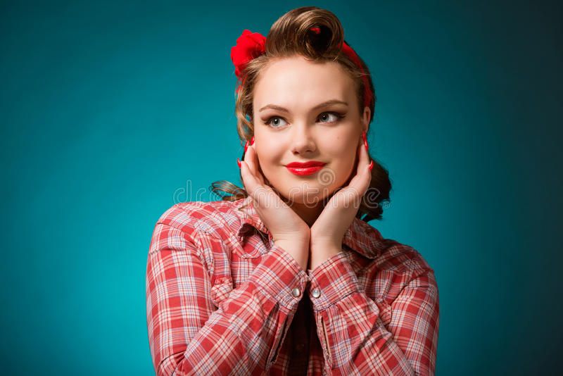 Pretty pinup girl in retro vintage 50`s style. Closeup young pretty pinup girl red button shirt looking aside teal color background retro vintage 50`s style stock image