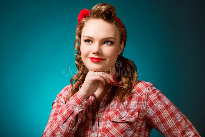 Pretty pinup girl in retro vintage 50`s style. Closeup young pretty pinup girl red button shirt looking up teal color background retro vintage 50`s style. Human royalty free stock image