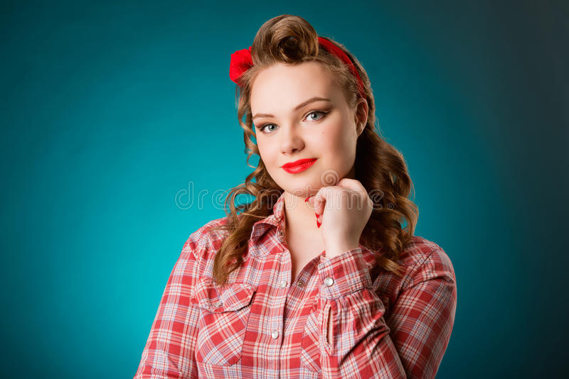 Pretty pinup girl in retro vintage 50`s style. Closeup young pretty pinup girl red button shirt looking at you camera teal color background retro vintage 50`s stock photo