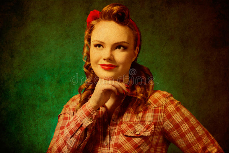 Pretty pinup girl in retro vintage 50`s style. Closeup young pretty surprise pinup girl red button shirt looking at you camera blue background retro vintage 50`s royalty free stock photography
