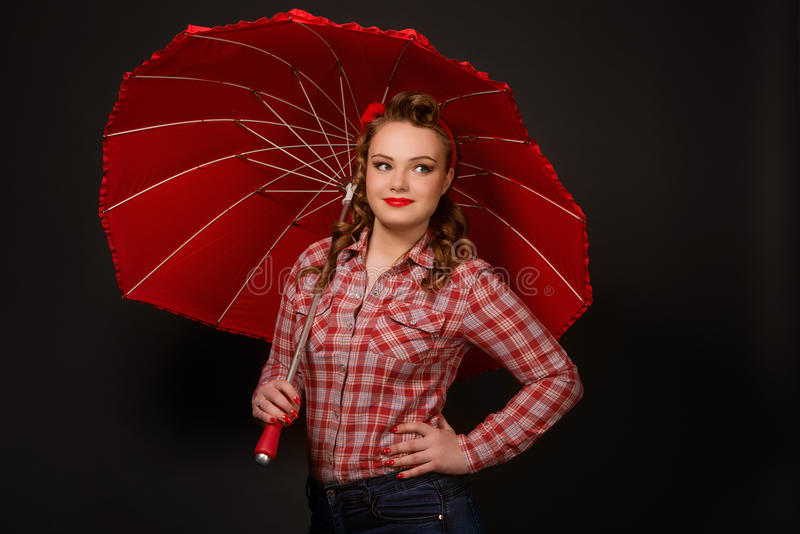 Pretty pinup girl in retro vintage 50`s style with red umbrella. Young pretty pinup girl red button shirt looking aside dark color background retro vintage 50`s stock photo