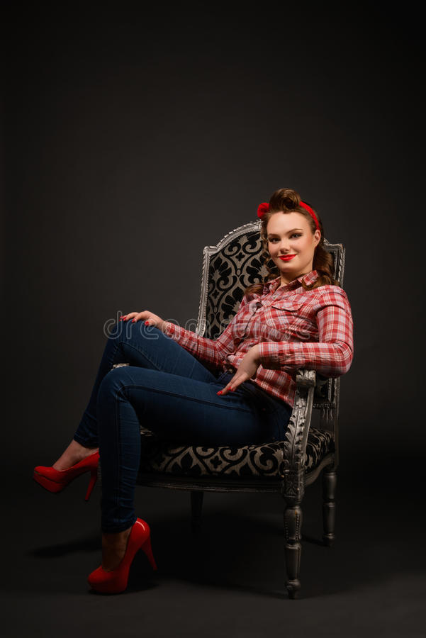 Pretty pinup girl in retro vintage 50`s style. Young pretty pinup girl red button shirt siting in chair dark background retro vintage 50`s style. Human emotions stock photo