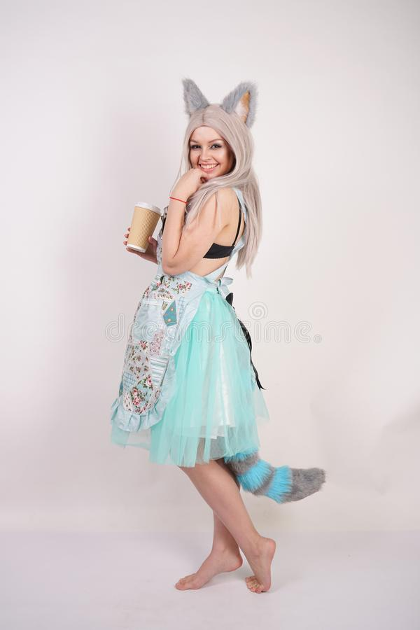 Pretty playful young girl with cat ears and long fluffy fur tail wearing kitchen apron on white background isolated. Alone royalty free stock image