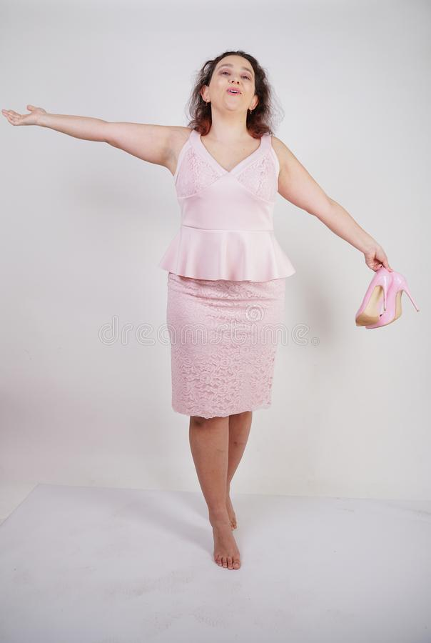 Pretty plump woman in pink dress with patent leather stiletto heels on white background in Studio. Isolated royalty free stock photography