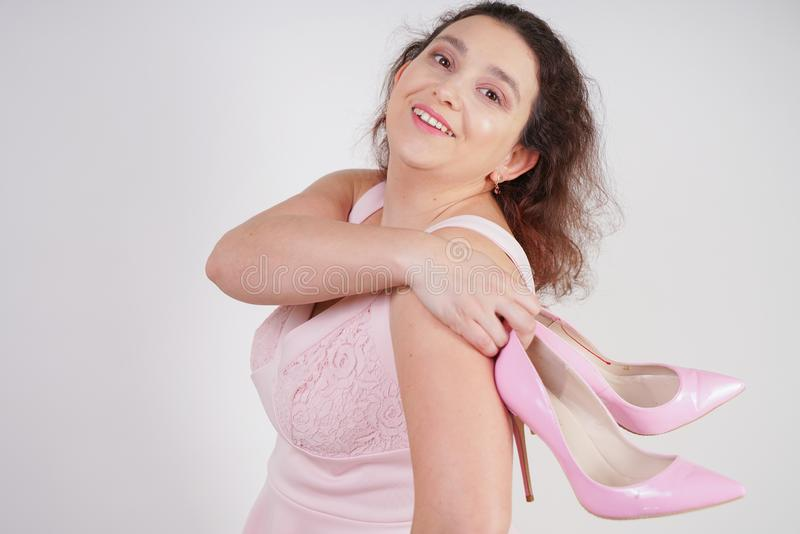 Pretty plump woman in pink dress with patent leather stiletto heels on white background in Studio stock photography