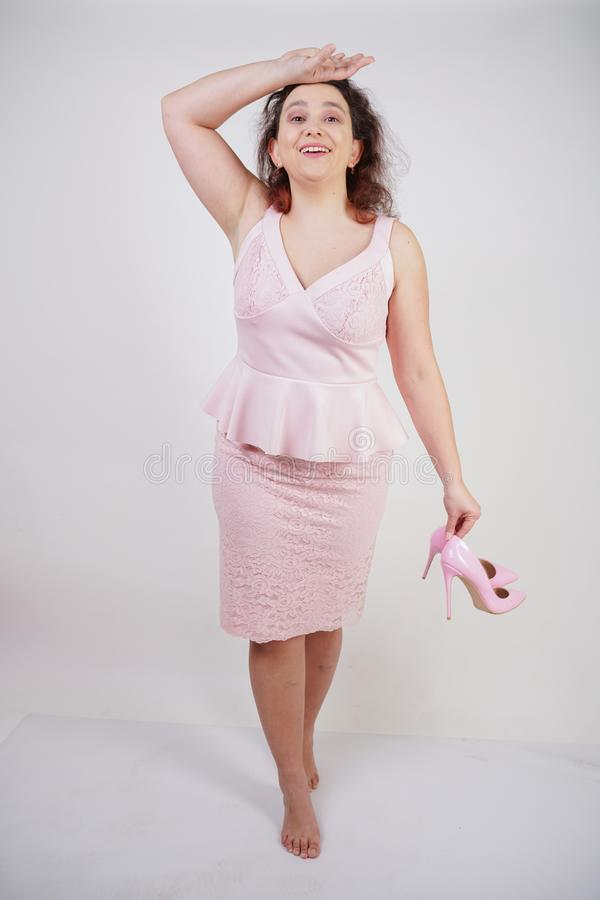 Pretty plump woman in pink dress with patent leather stiletto heels on white background in Studio stock image